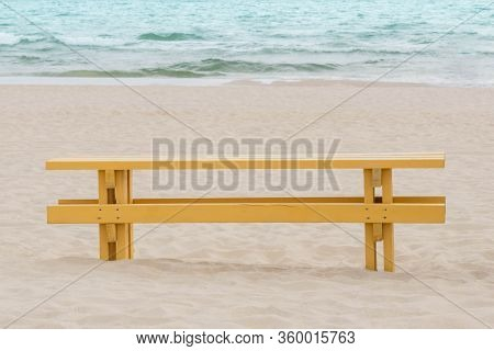 Solitary Bench On San Beach Overlooking Sea. Empty Yellow Bench On The Seafront. Wooden Bench On San