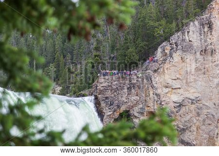Yellowstone National Park, Usa - July 12 2014:  A Group Of Tourists Standing On A Cliff At A Viewpoi