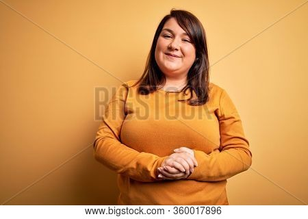 Beautiful brunette plus size woman wearing casual sweater over isolated yellow background with hands together and crossed fingers smiling relaxed and cheerful. Success and optimistic