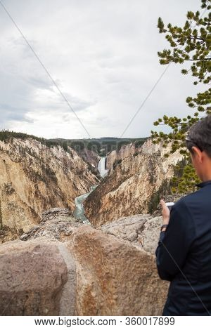 Yellowstone National Park, Usa - July 12 2014:  A Tourist Taking Cell Phone Pictures From The Viewpo