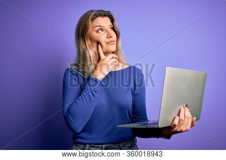 Young beautiful blonde woman working using laptop over isolated purple background serious face thinking about question, very confused idea