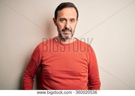 Middle age hoary man wearing casual orange sweater standing over isolated white background Relaxed with serious expression on face. Simple and natural looking at the camera.