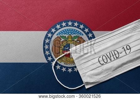 Face Medical Surgical White Mask With Covid-19 Inscription Lying On Missouri State Flag. Coronavirus