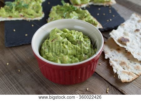 Guacamole Sauce In The Red Ramekin On A Wooden Surface With Toasted Tortillas On A Black Slate Plate
