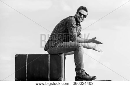 Travel Agency. Man Sit On Suitcase Before Journey. Business Trip. Handsome Guy Traveler. Guy Outdoor