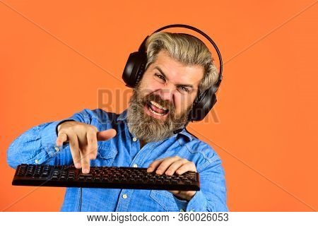 Man Bearded Hipster Gamer Headphones And Keyboard. Gaming Addiction. Superior Performance. Online Ga