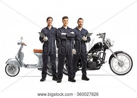 Full length portrait of motorcycle mechanic workers in uniforms posing next to motorbikes isolated on white background