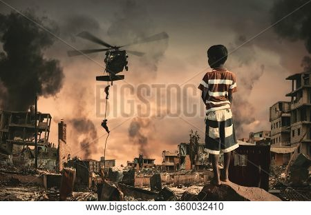 Homeless Little Boy Watching Roping Soldier In Destroyed And Bombarded City Between Smoke.