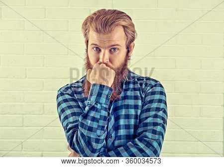Thinking. Portrait Of A Worried Man Casual Blue Shirt Man Looking At You Camera Isolated White Brick