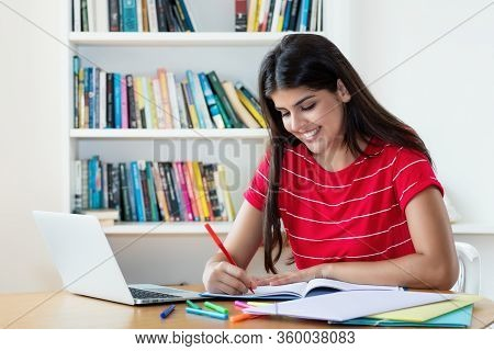 Laughing Hispanic Female Student Learning Language Online Using Computer At Home
