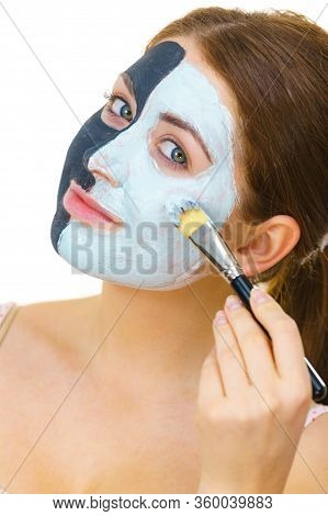 Woman With Clay Carbo Black Mask On Half Face Applying White Mud To Clean Skin. Girl Taking Care Of