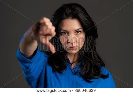 Adult Woman Standing On Grey Studio Background Showing Thumb Down Gesture And Expressing Discontent