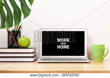 Stylish home studio workspace with computer, supplies and coffee cup. Work from home concept.