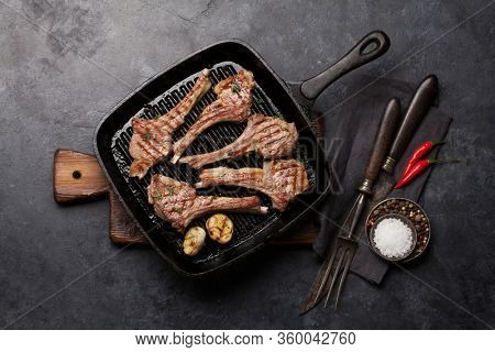 Grilled lamb ribs in frying pan. Hot rack of lamb with spices and condiments. Top view on stone table