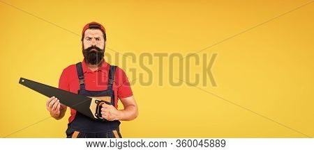 Brutal Male Worker With Saw. Man Builder Yellow Background. Professional Repairman In Uniform. Build