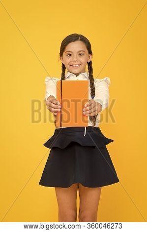 Love Reading For Pleasure. Cute Small Schoolchild Holding Reading Book On Yellow Background. Adorabl