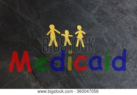Paper Family Of Three With Colorful Medicaid Text On Textured Surface
