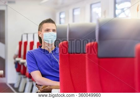 Young Man Traveling By Train And Wears A Mask