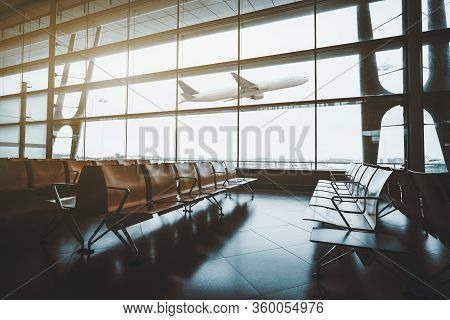 A Dark Interior Of A Waiting Hall Near Departure Gates Of A Modern Airport Terminal With Rows Of Emp