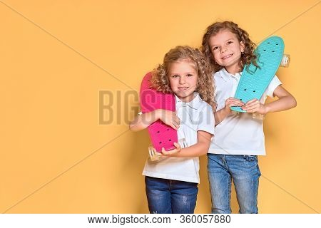 Two Active And Happy Girls With Curly Hair Having Fun With Penny Board, Smiling Face Stand Skateboar