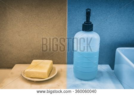 Soap bar versus liquid hand soap bottle comparison of hand washing products on home bathroom vanity. Yellow and blue color boxes to compare.