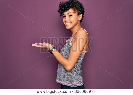 Young beautiful african american afro sportswoman doing exercise wearing sportswear pointing aside with hands open palms showing copy space, presenting advertisement smiling excited happy