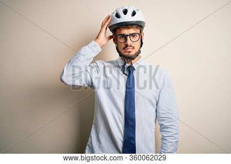 Young businessman wearing glasses and bike helmet standing over isolated white bakground confuse and wonder about question. Uncertain with doubt, thinking with hand on head. Pensive concept.