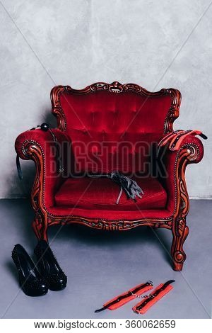 Set Of Erotic Toys For Bdsm On Red Chair