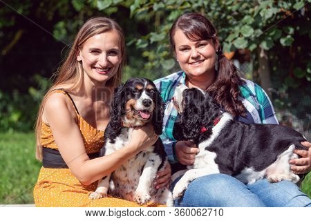 Two girlfriends having fun with dogs in the animal sanctuary getting to know them