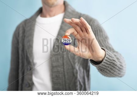American Democracy Elections. Unrecognizable American Citizen Holding Voting Pin On Blurred Blue Bac