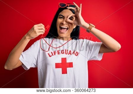 Young beautiful hispanic lifeguard woman wearing safeguard t-shirt holding whistle with happy face smiling doing ok sign with hand on eye looking through fingers