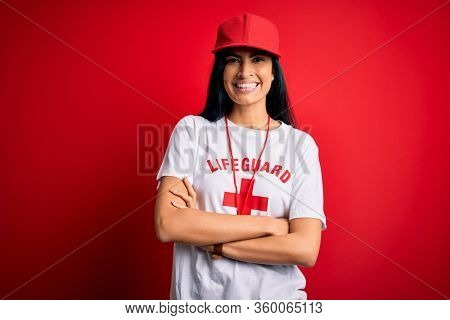 Young beautiful hispanic lifeguard woman wearing safeguard t-shirt and whistle happy face smiling with crossed arms looking at the camera. Positive person.