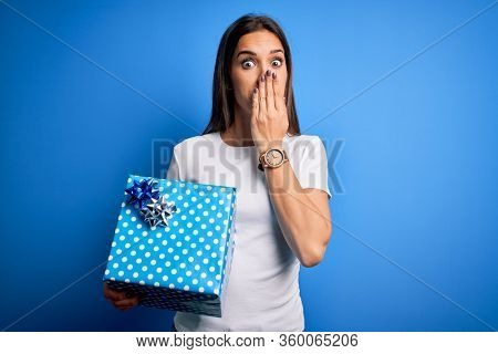 Young beautiful brunette woman holding birthday gift over isolated blue background cover mouth with hand shocked with shame for mistake, expression of fear, scared in silence, secret concept