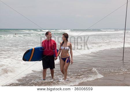 man with surf and the girl go on an ocean coast