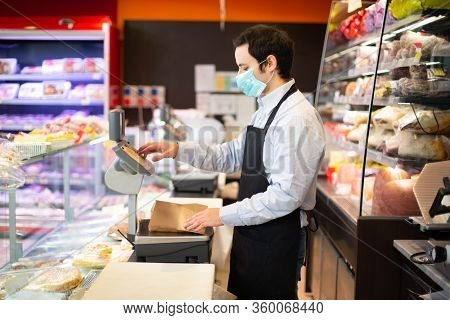 Shopkeeper running his business while wearing a mask, coronavirus pandemic concept