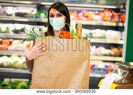 Masked woman holding an healthy food bag in a grocery store