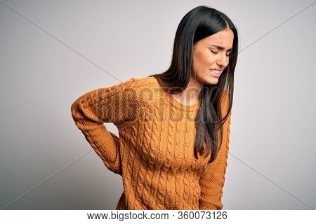 Young beautiful brunette woman wearing casual sweater over isolated white background Suffering of backache, touching back with hand, muscular pain