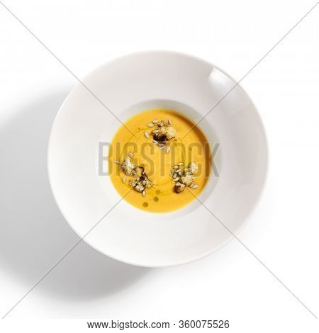Pumpkin soup in white bowl. Served main course top view. Vegetable cream soup decorated with seeds. Restaurant food portion, main course. Vegetarian supper. Dinner, gourmet meal in plate