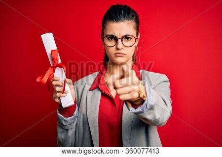 Young beautiful brunette student woman wearing glasses holding university degree diploma pointing with finger to the camera and to you, hand sign, positive and confident gesture from the front