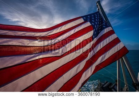 American Flag Backlit With Early Morning Sun On Boat In Florida Keys