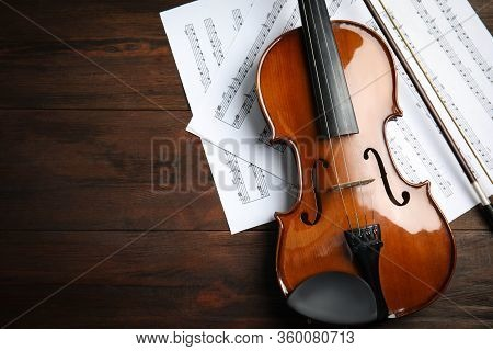 Beautiful Violin, Bow And Note Sheets On Wooden Table, Flat Lay. Space For Text