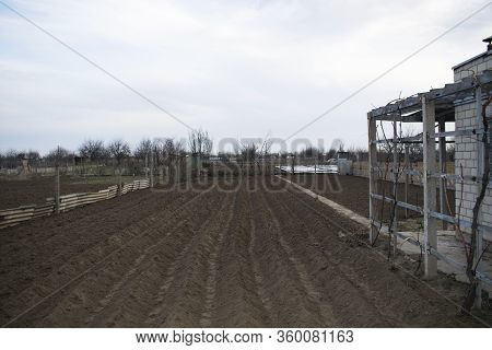 Land Dug Up A Large Plot Near A Country House. Plowed Land Is Ready For Planting Potatoes. Seasonal