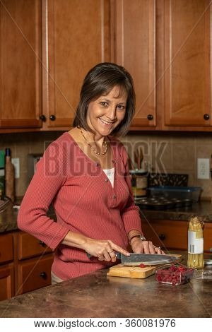 Mature woman preparing a meal at home cutting berries