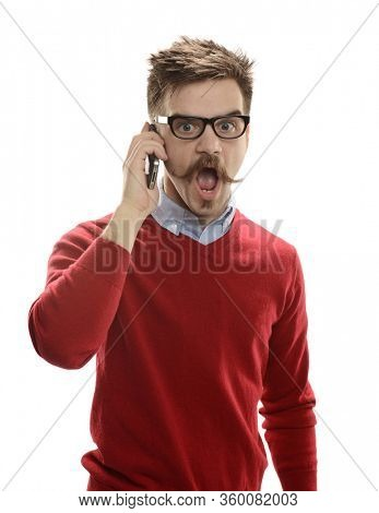 Young man on the cell phone with wide open mouth expressing surprise isolated on a white background