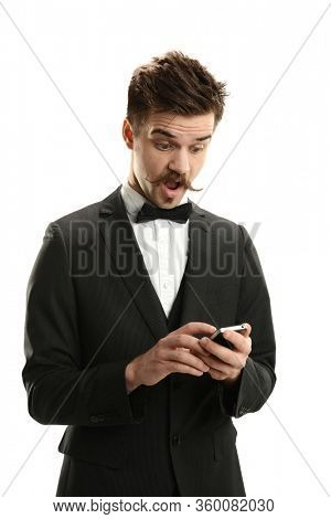 Young man cheching his smart phone expressing surprise isolated on a white  backround