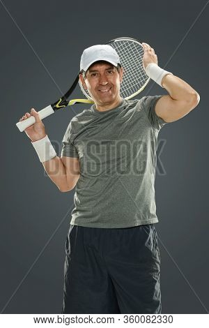 Mature man holding tennis racket behind his head isolated on a gray background