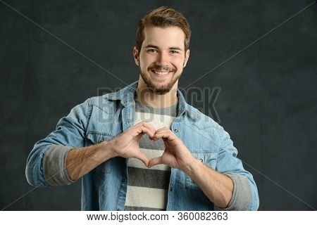 Cassual young man making a heart shape with his hands against a gray background