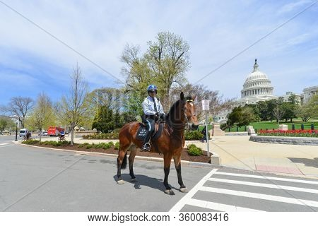 Washington DC / United States - April 21 2014:  A mounted policeman in front of United States Capitol Building in Washington DC.