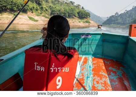 Nakhon Nayok, Thailand - February 2, 2020 : Young Thai Girl Wears Orange Life Vest With Name Of Boat