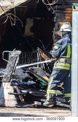 A Strong And Brave Fireman Rescues A Burning Building Using Water In A Fire Operation. Fireman In A